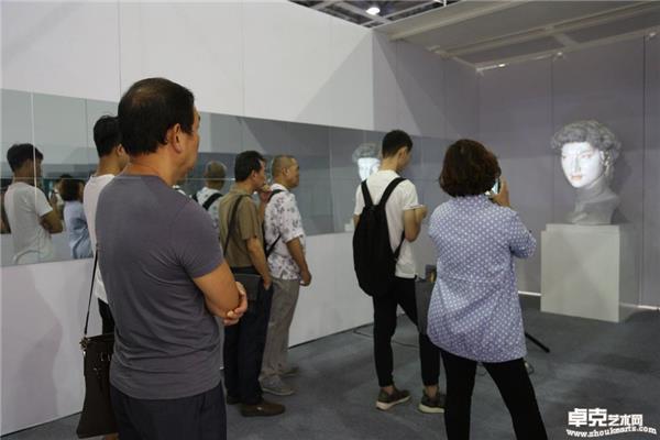 展览现场观众认真地观赏作品《变脸——西方邂逅东方》